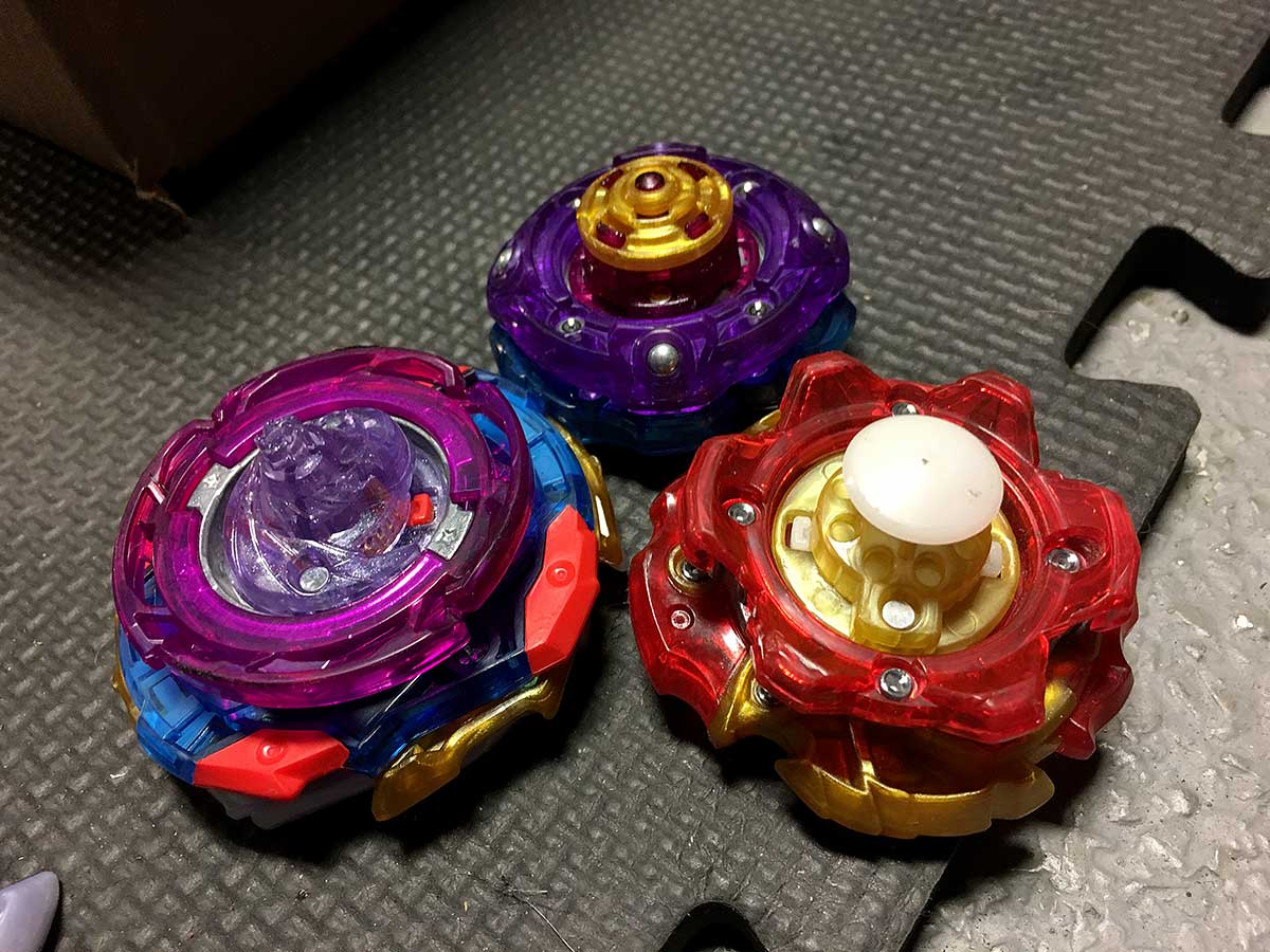 bottom view of three beyblades imperial with expand and spiral dash lord vanguard bearing and archer with around xtend plus