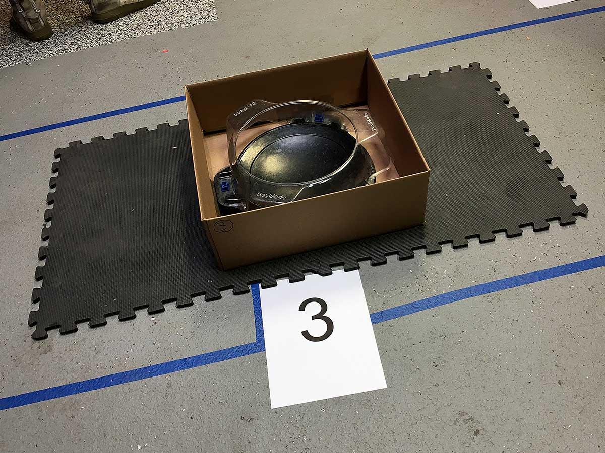 black beystadium inside cardboard box on foam mats with number 3 sign in front of it