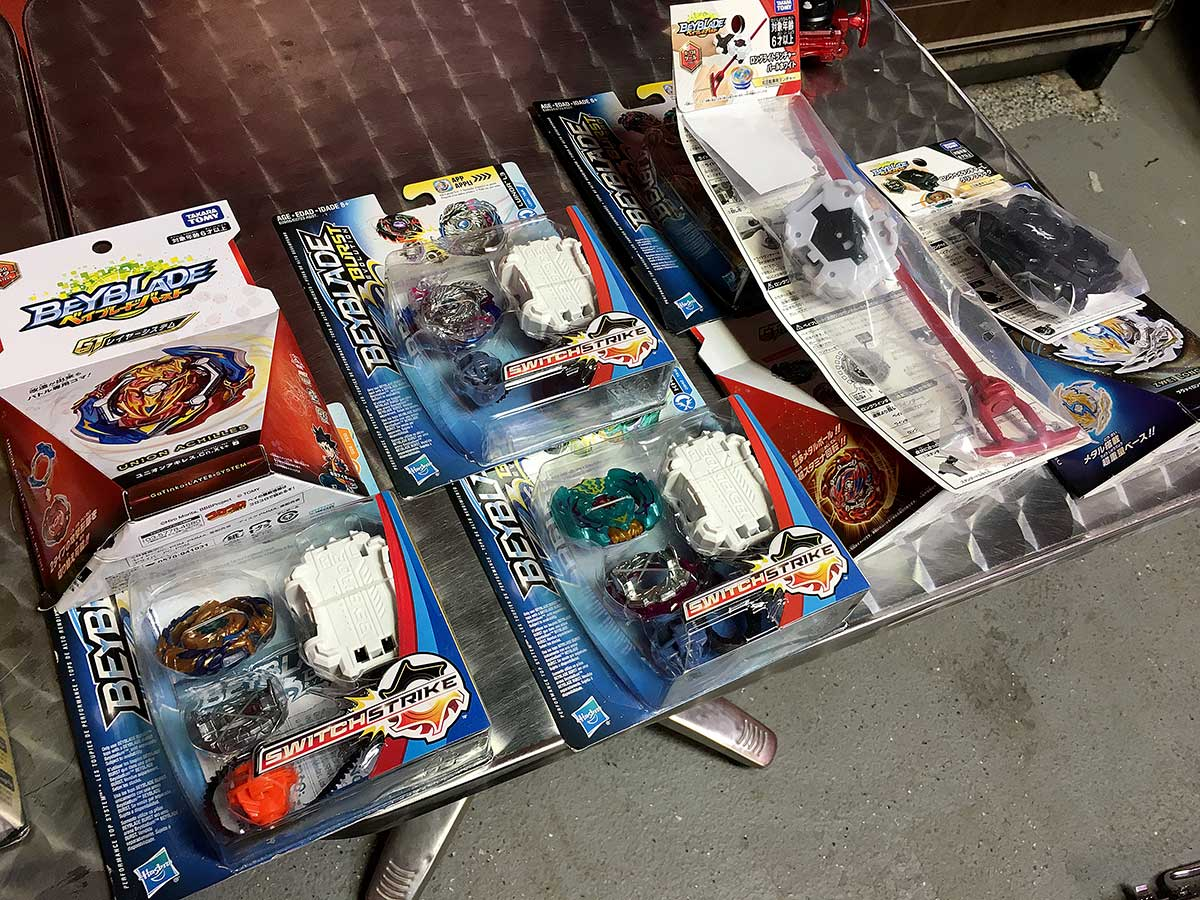 variety of new beyblade burst products on metal table