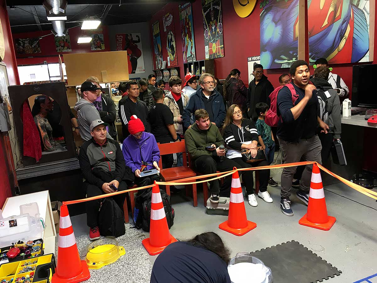 crowd watching beyblade matches at tournament in comic book shop