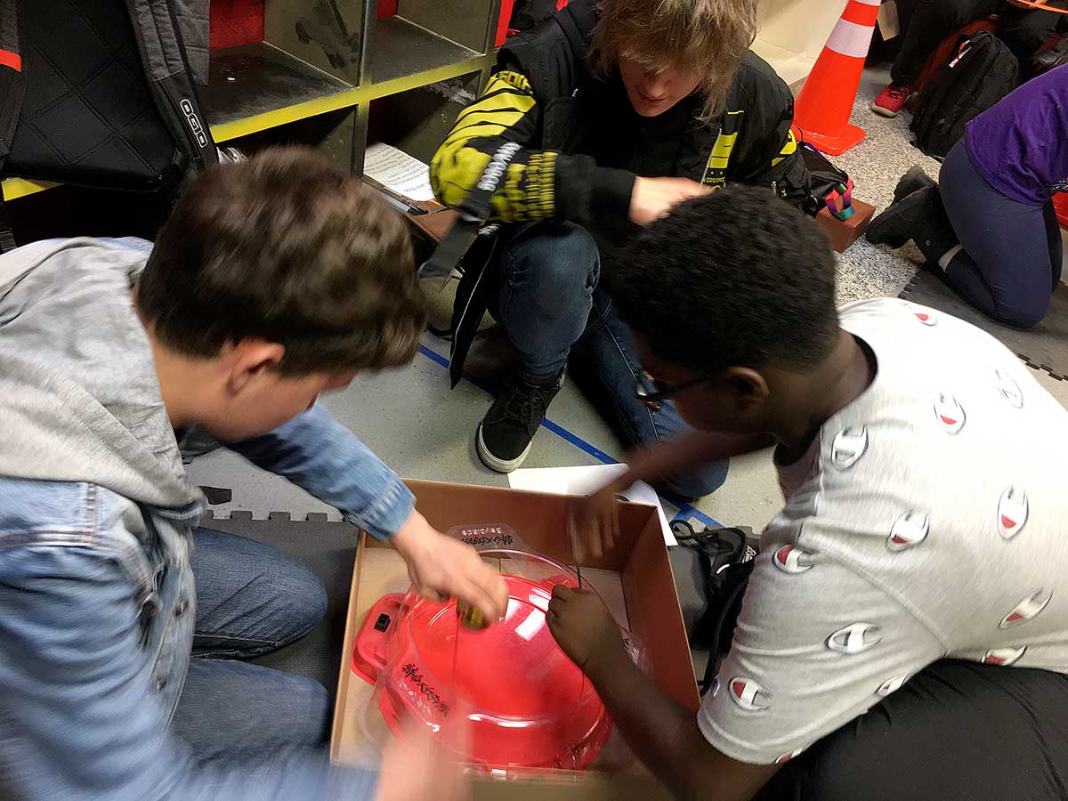 two boys playing beyblade at tournament with judge looking into stadium