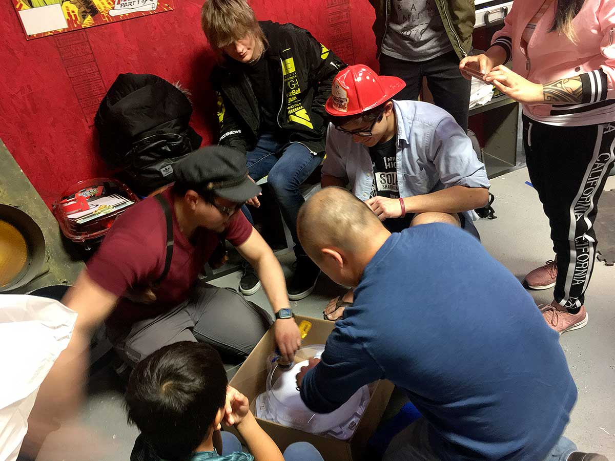 two men playing beyblade at tournament with judge looking into stadium