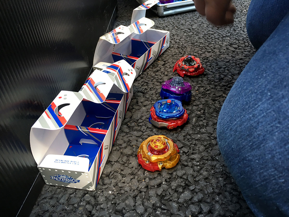 four beyblades in front of two 3on3 beyblade burst deck boxes