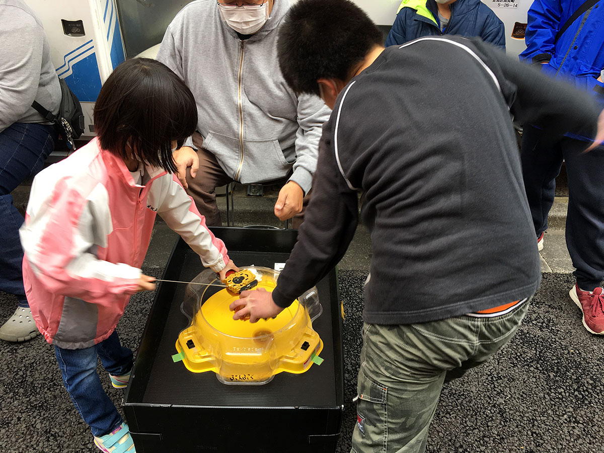 girl and boy launching beyblades into yellow beystadium