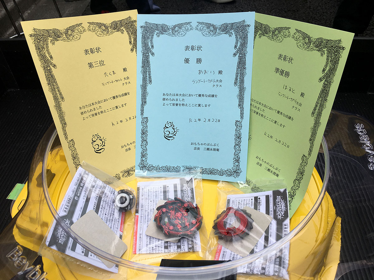 certificates and prizes for beyblade tournament sitting inside stadium