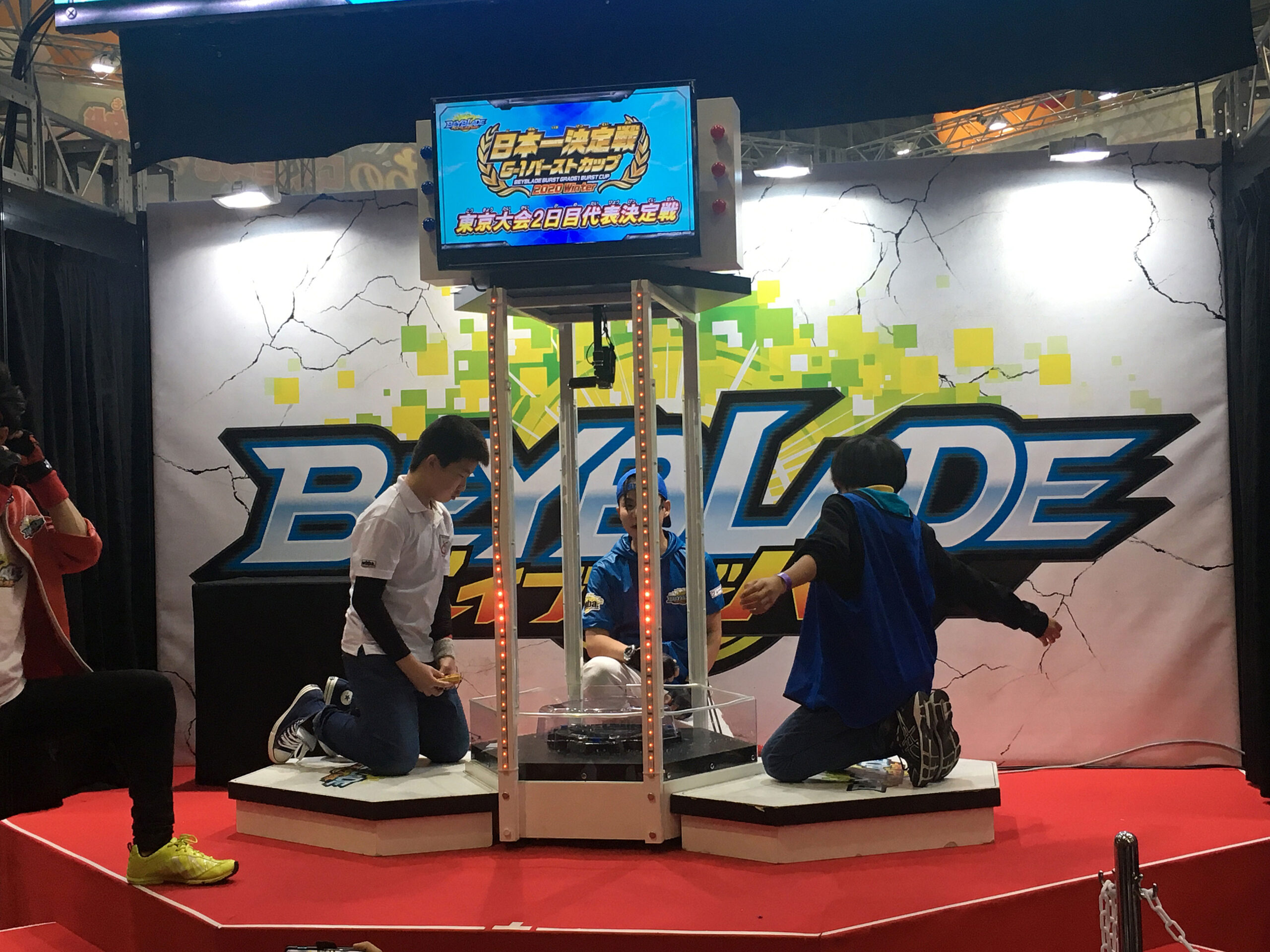 two boys at stadium on stage with judge during g1 beyblade burst tournament finals