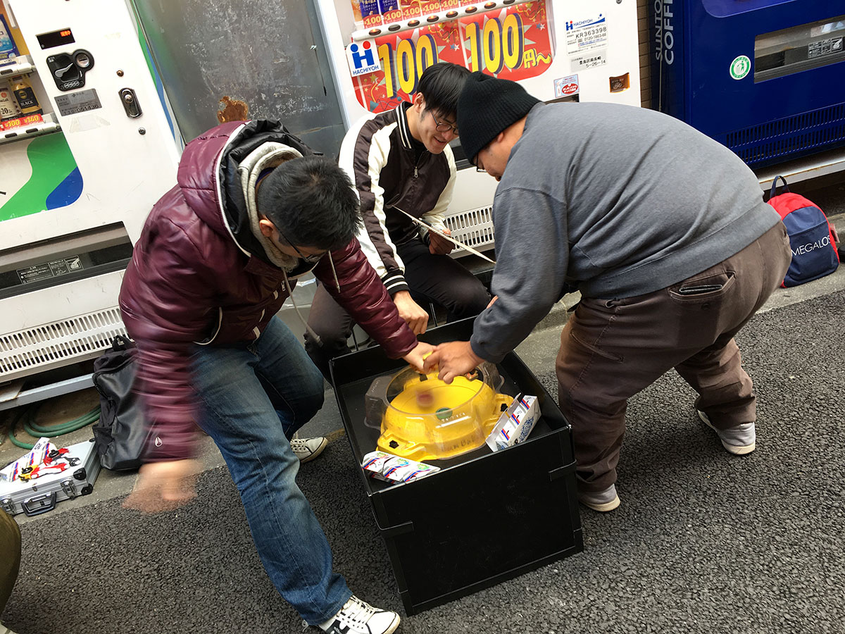 two men launching beyblades into yellow beystadium