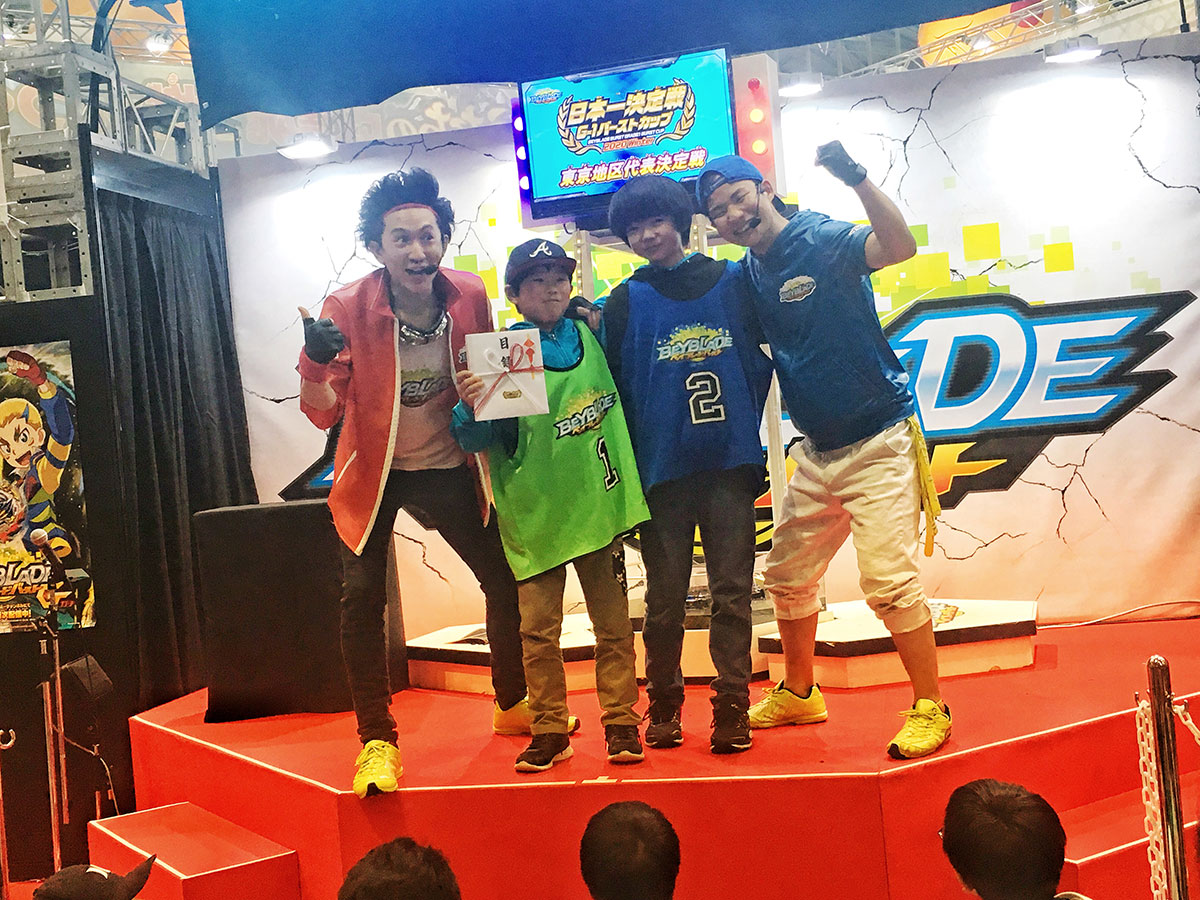 beyblade burst grade 1 tournament winners on stage with judges
