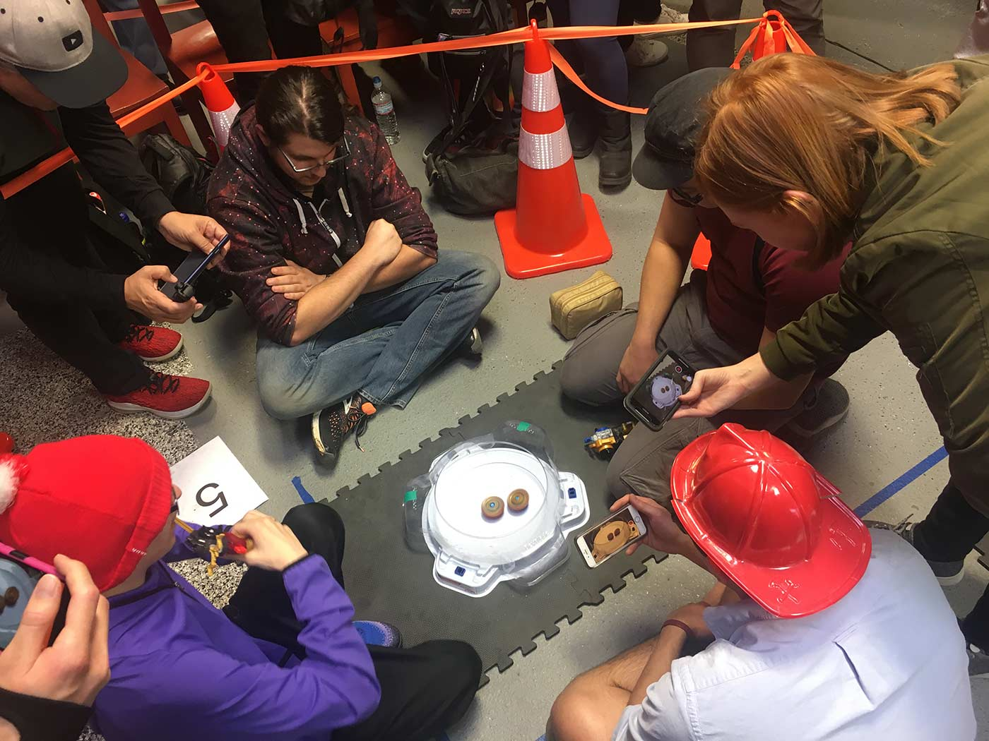 Top down view of Yami judging match between Zankye and King Loofa at WBO Beyblade Tournament in Los Angeles, Beyblade West