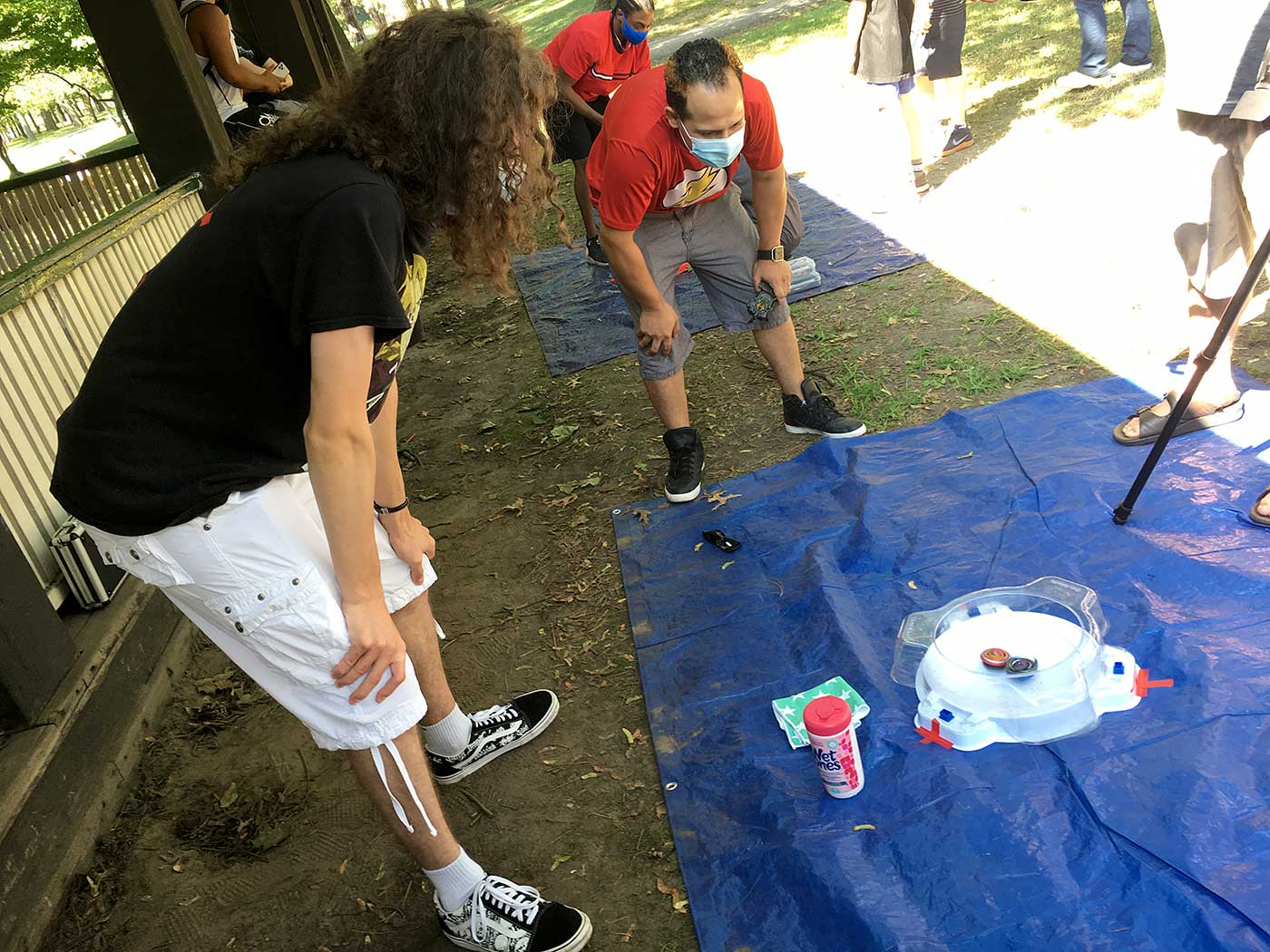 judge and player observing beyblades in stadium at outdoor beyblade tournament
