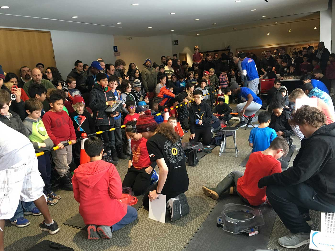 large group of people spectating indoor beyblade tournament
