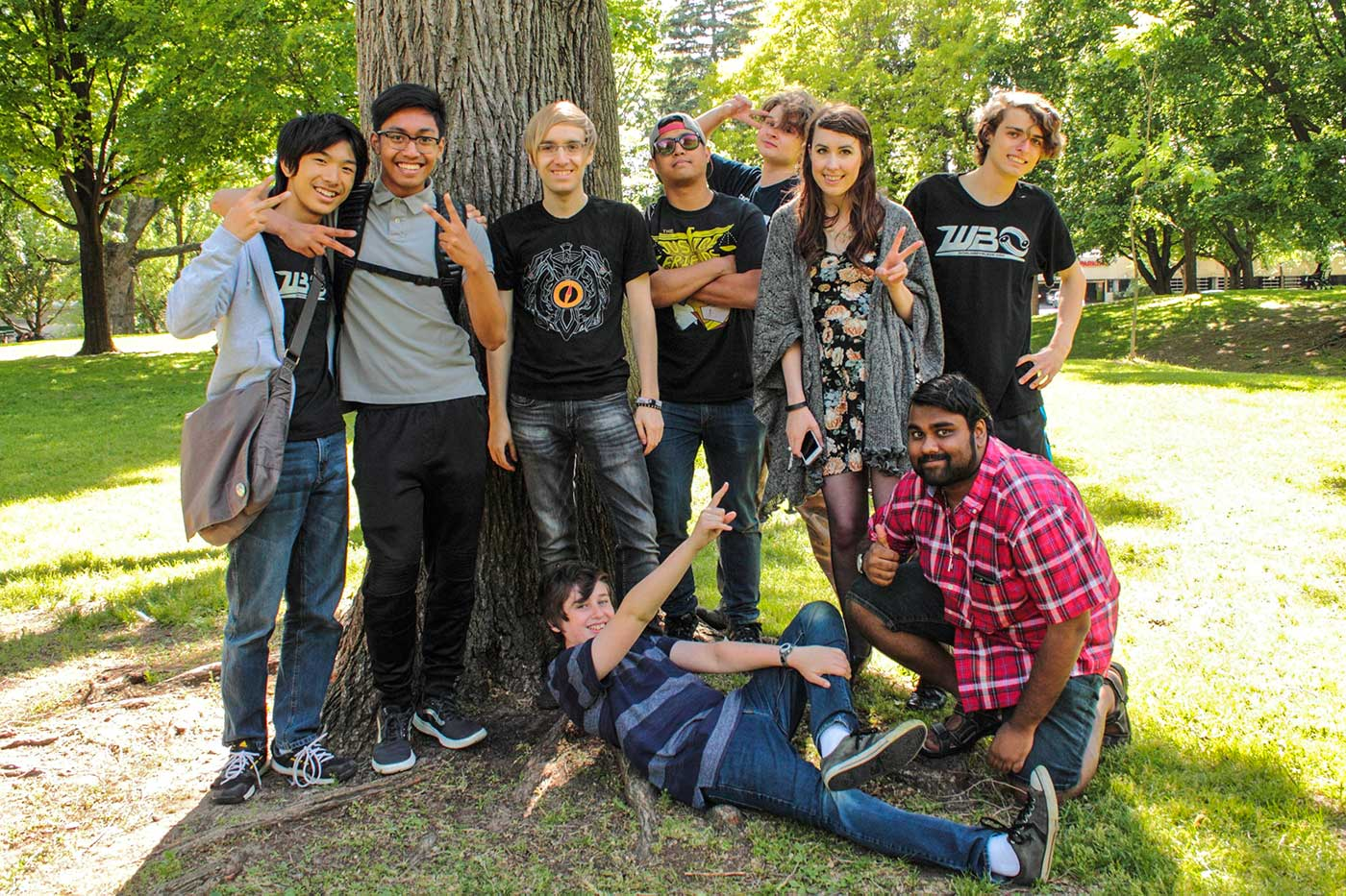 group photo of nine people in front of tree in park