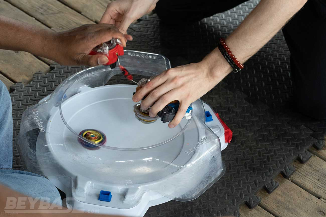 two players launching beyblades into white stadium