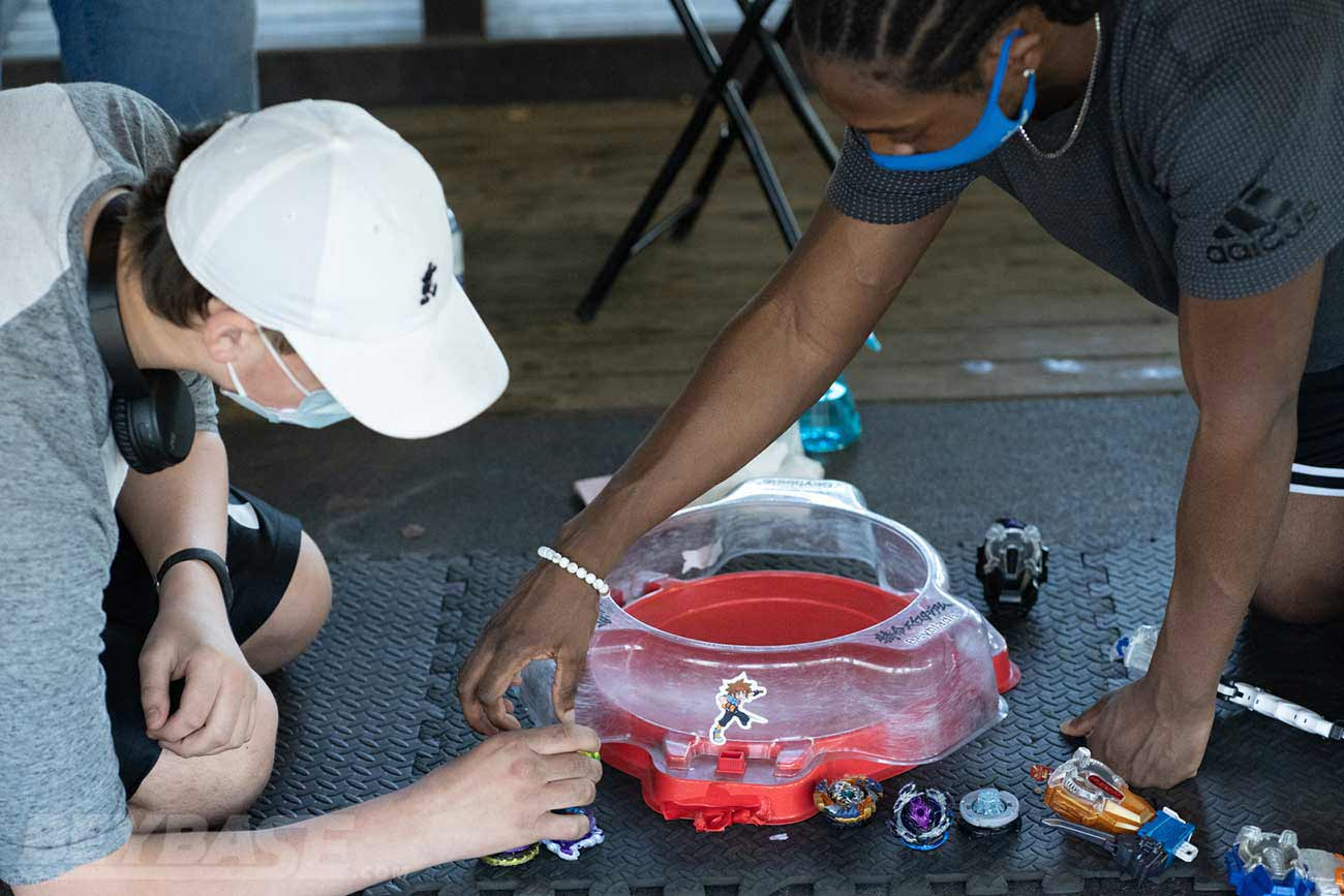 two players inspecting sets of beyblades sitting beside red stadium
