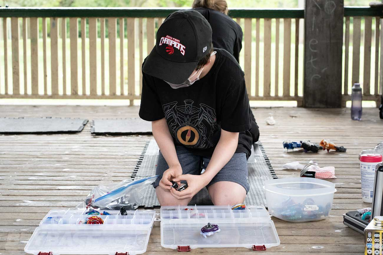 boy wearing black shirt and hat looking over opened plastic beyblade parts cases
