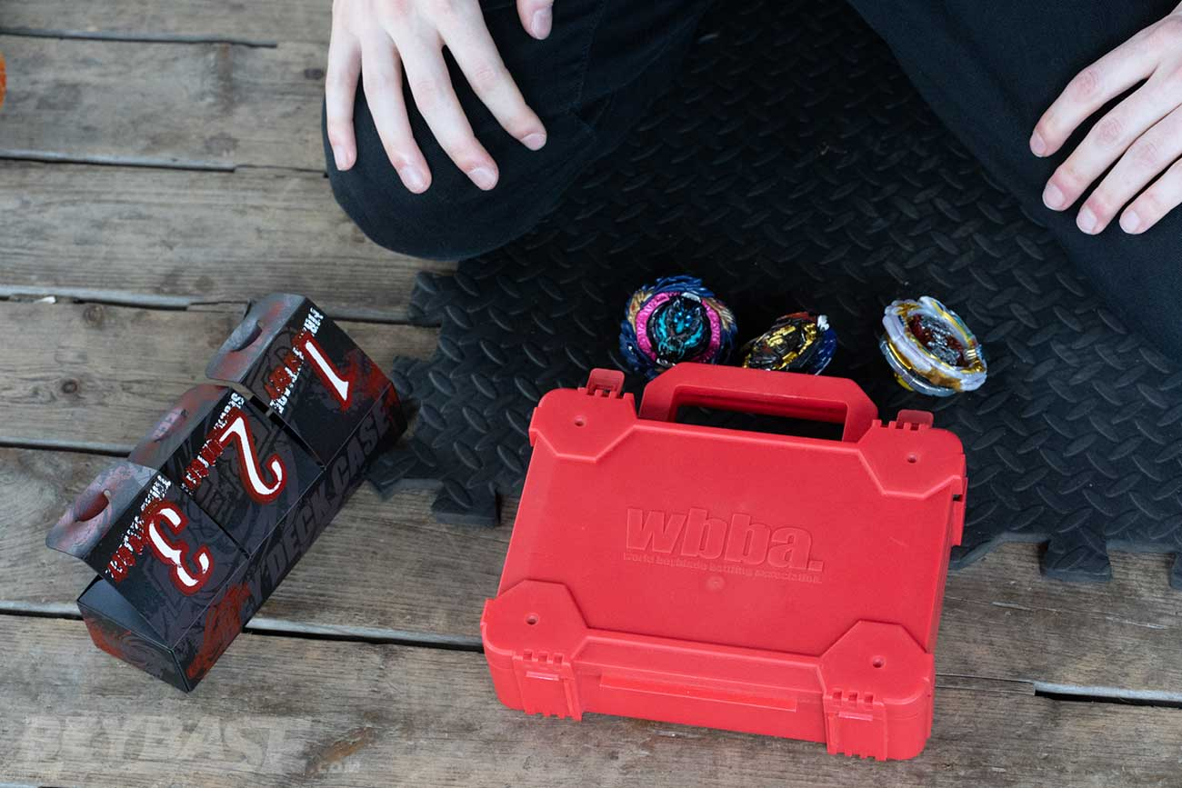 beyblade deck box and wbba deck box with three beyblades sitting on the ground outside it