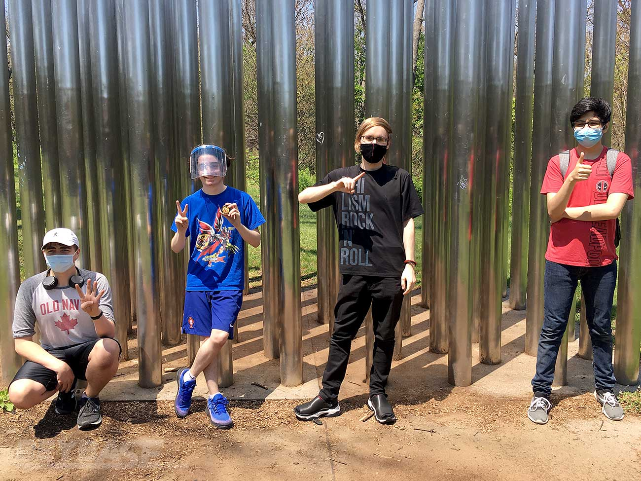 four people standing in front of outdoor art installation of tall metal poles