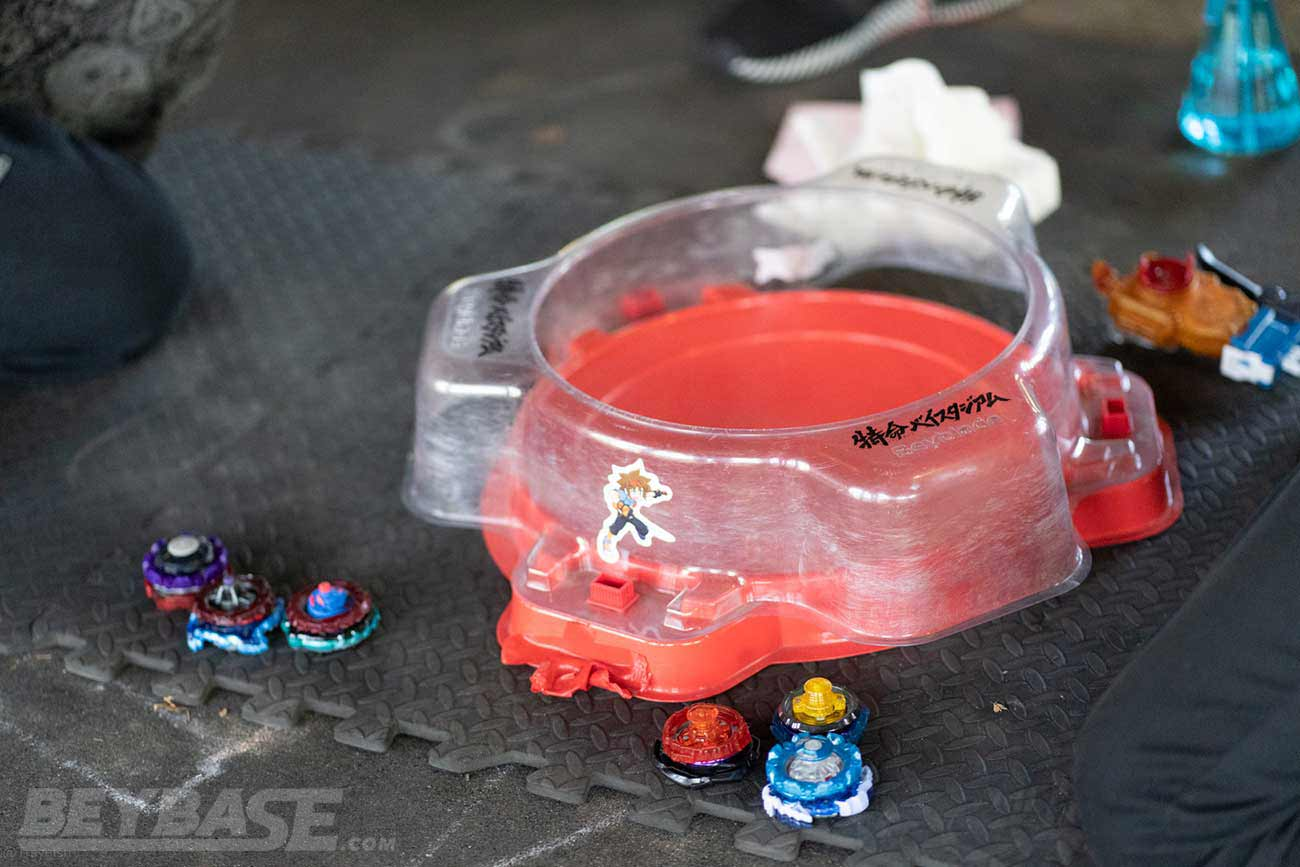 two sets of three beyblades sitting beside red stadium