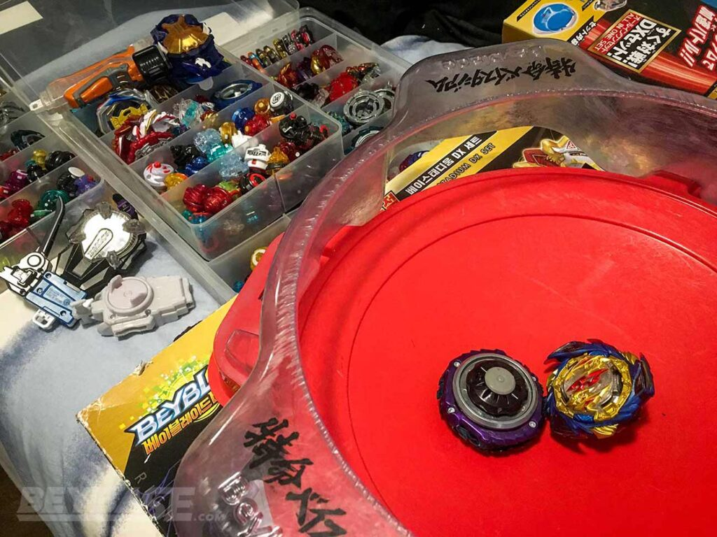 two beyblades sitting inside beyblade burst stadium and opened cases with hundreds of parts
