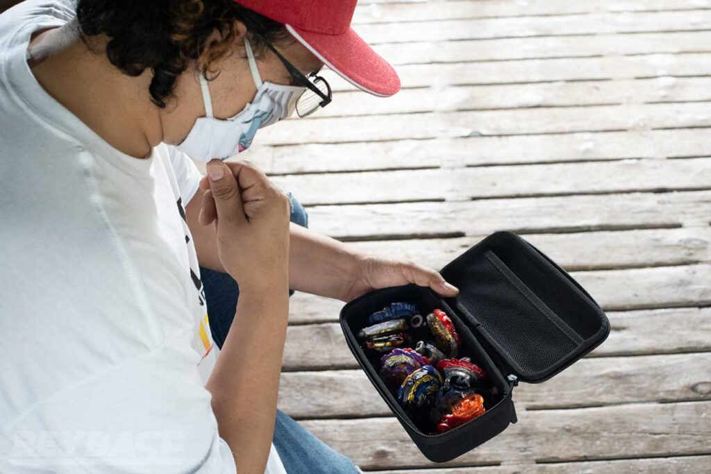 man wearing white shirt and red hat looking down into open black case filled with Beyblades