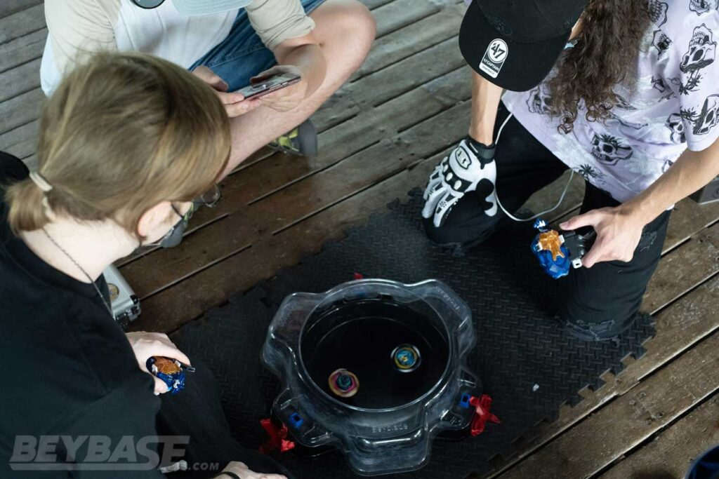 overhead view of kei and 1234beyblade looking down at beyblades in stadium